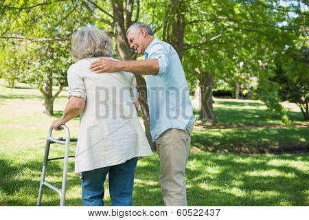 Rear view of a mature man assisting woman with walker at the park
