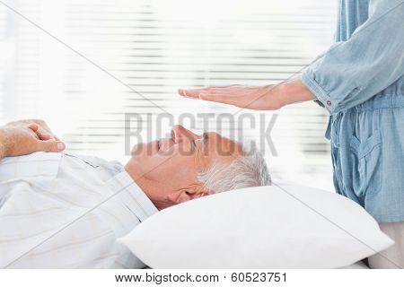 Massage therapist performing Reiki over senior man at health spa
