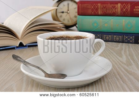 A Cup Of Coffee On The Table Against The Background Of An Open Book