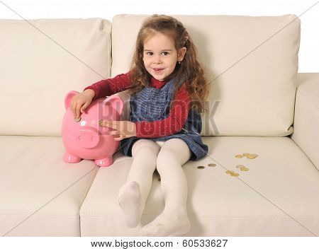 Cute Little Girl Playing With Coins And Huge Piggy Bank On Sofa