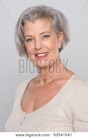 Smiling senior woman in front of grey background