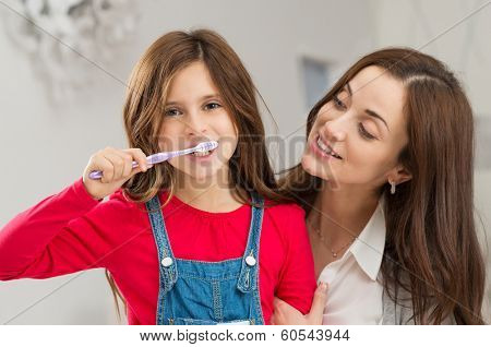 Happy Young Mother Looking At Her Daughter Brushing Teeth