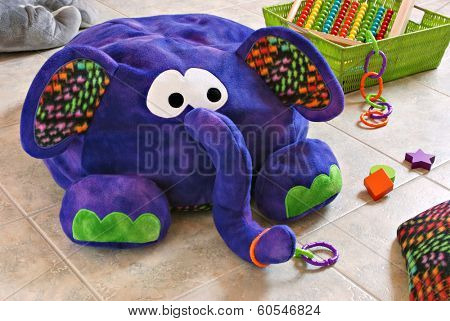 Colorful stuffed elephant with pillow and basket of toys on tile in kids playroom.  (Elephant is a handcrafted beanbag floor pillow made of fleece fabric)