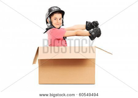 Playful boy with helmet sitting in carton box isolated on white background