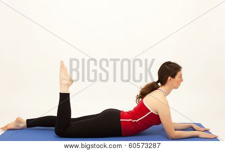 The Young Woman Is Exercising On A Mat