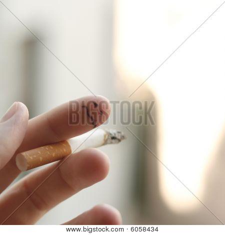 Sad smiley on smoking finger