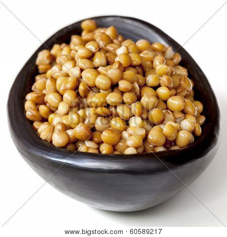 Lentils in black stoneware bowl, isolated on white.