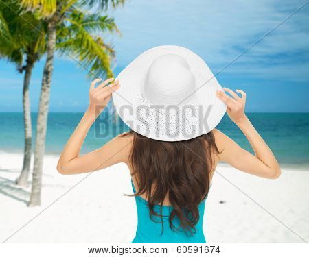 summer and vacation concept - woman sitting in swimsuit with hat