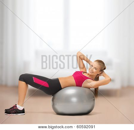 fitness, gym, exercise and health concept - young woman doing exercise on fitness ball at home