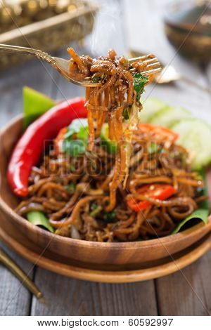 Indonesian and Malaysian cuisine, spicy fried noodles, mi goreng or mee goreng mamak with wooden dining table setting. Fresh hot with steamed smoke.