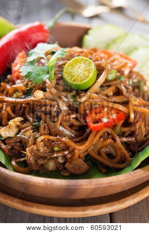 Indonesian and Malaysian cuisine, mi goreng or mee goreng mamak,  spicy fried noodles with wooden dining table setting. Fresh hot with steamed smoke.