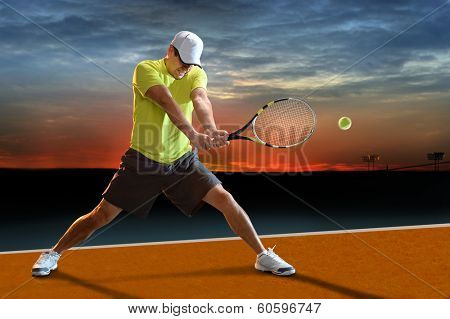 Mature Hispanic tennis player swinging racket at sunset