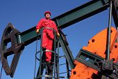 stock photo of crude-oil  - Worker in action at pump jack oil well - JPG
