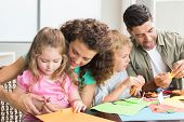 stock photo of paper craft  - Cheerful family doing arts and crafts together at the table at home in kitchen - JPG