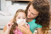 image of cold-shoulder  - Mother helping her daughter blow her nose at home in living room - JPG