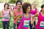 Smiling female participants of breast cancer marathon running in park