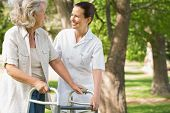 Smiling young female assisting mature woman with walker at the park