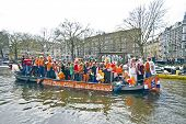 AMSTERDAM - APRIL 30: Amsterdam canals full of boats and people in orange during the celebration of