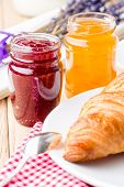 Raspberry and orange jam with croissant.
