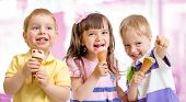 stock photo of threesome  - happy children or kids group with ice cream - JPG