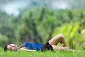 Beautiiful young Filipina woman relaxing on green grass lying on her back in a lush green park looki