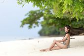 image of filipina  - Beautiful Filipina woman sitting in her bikini on a tropical beach in her bikini on the golden sand in the shade of a green leafy tree looking out towards the ocean - JPG