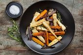 stock photo of onion  - Roasted root vegetables on a black serving platter - JPG