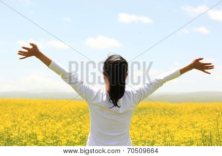 Cheering woman open arms at cole flower field