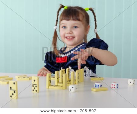 Cheerful Child Playing With Small Toys At Table