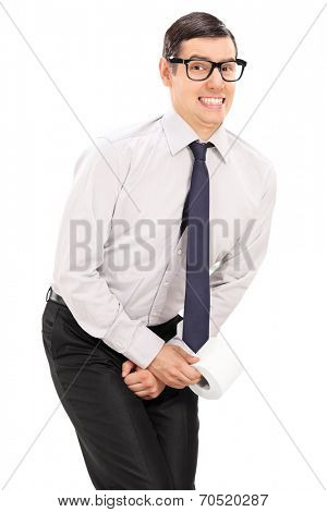 Vertical shot of a man needing to urinate and holding a toilet paper isolated on white background