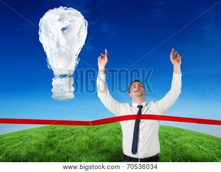 Composite image of businessman crossing finishing line against cloud light bulb