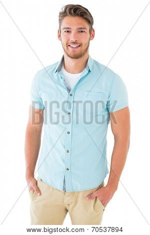 Handsome young man posing with hands in pockets on white background