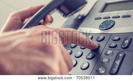 Man Dialling Out On A Landline Telephone