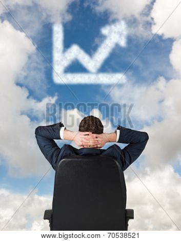 Businessman sitting in swivel chair against blue sky with white clouds