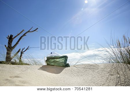 Plastic bag filled with empty bottles on a sunny beach