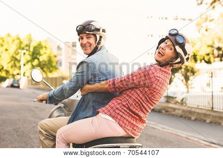 Happy mature couple riding a scooter in the city on a sunny day
