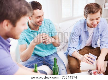 leisure, games, friendship, gambling and entertainment - three smiling male friends playing cards and drinking beer at home