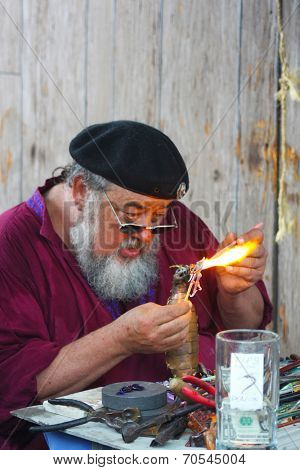 MUSKOGEE, OK - MAY 24: An old man uses fire to create a piece of art at the Oklahoma 19th annual Renaissance Festival on May 24, 2014 at the Castle of Muskogee in Muskogee, OK.