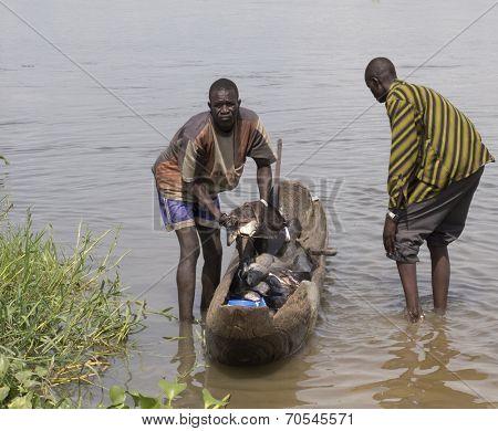 BOR, SOUTH SUDAN-JUNE 26 2012: Unidentified fishermen haul fish out of a canor in Bor, South Sudan.