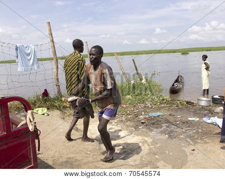 BOR, SOUTH SUDAN-JUNE 26 2012: Unidentified fisherman hauls catfish out of the Nile River in South Sudan