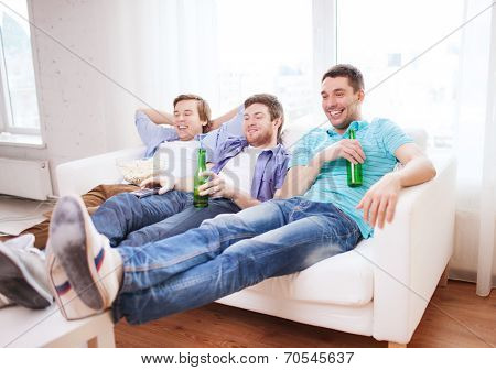 friendship, home, sports and entertainment concept - happy male friends with beer watching tv at home