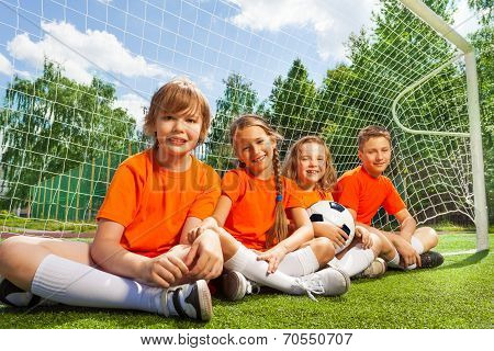 Happy children sitting together on field grass