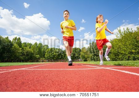 Two boys run while competing to each other