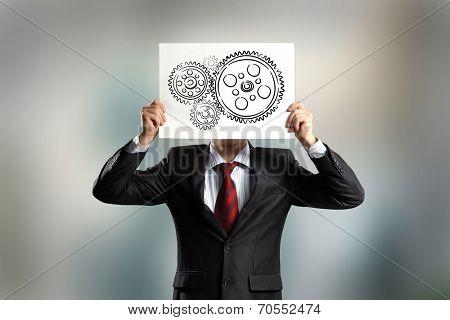 Businessman hiding face behind paper sheet. Working business mechanism