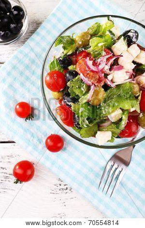 Glass bowl of Greek salad served on napkin on wooden background