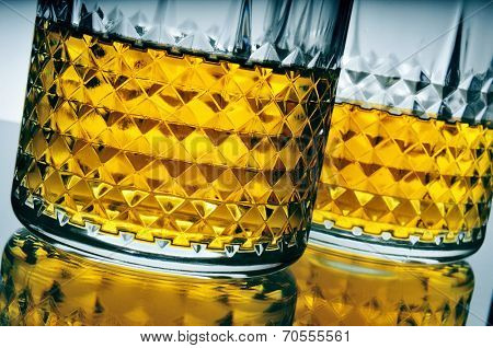 closeup of some lowball glasses with whisky on a reflecting surface