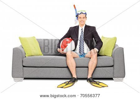 Man with snorkel and business suit seated on sofa isolated on white background