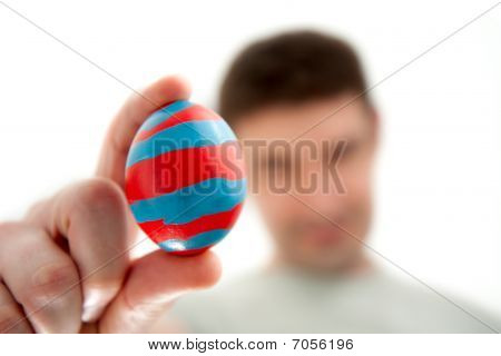 Man Holding A Striped Easter Egg