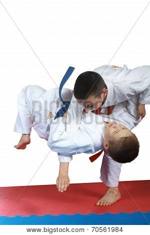 Boy with orange belt is doing throw judo