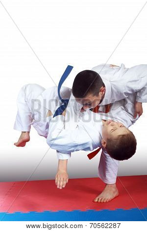 Two athletes in judogi are doing throws
